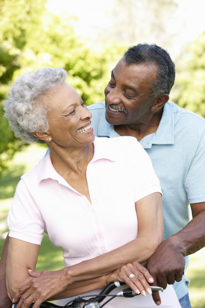 Senior African American Couple Cycling In Park smiling because of healthy smiles help by the menu of restorative dentistry services at Sterling Dental in Sterling CO.